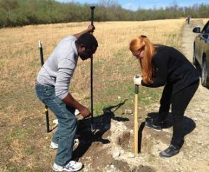 Oyeniyi Abe (left) of Nigeria and Raffaella Taylor-Seymour of London dig a post hole for a new fence on a former strip mine site.