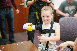 Alex Pring first tries his new bionic arm. Photo Credit: KT Crabb Photography
